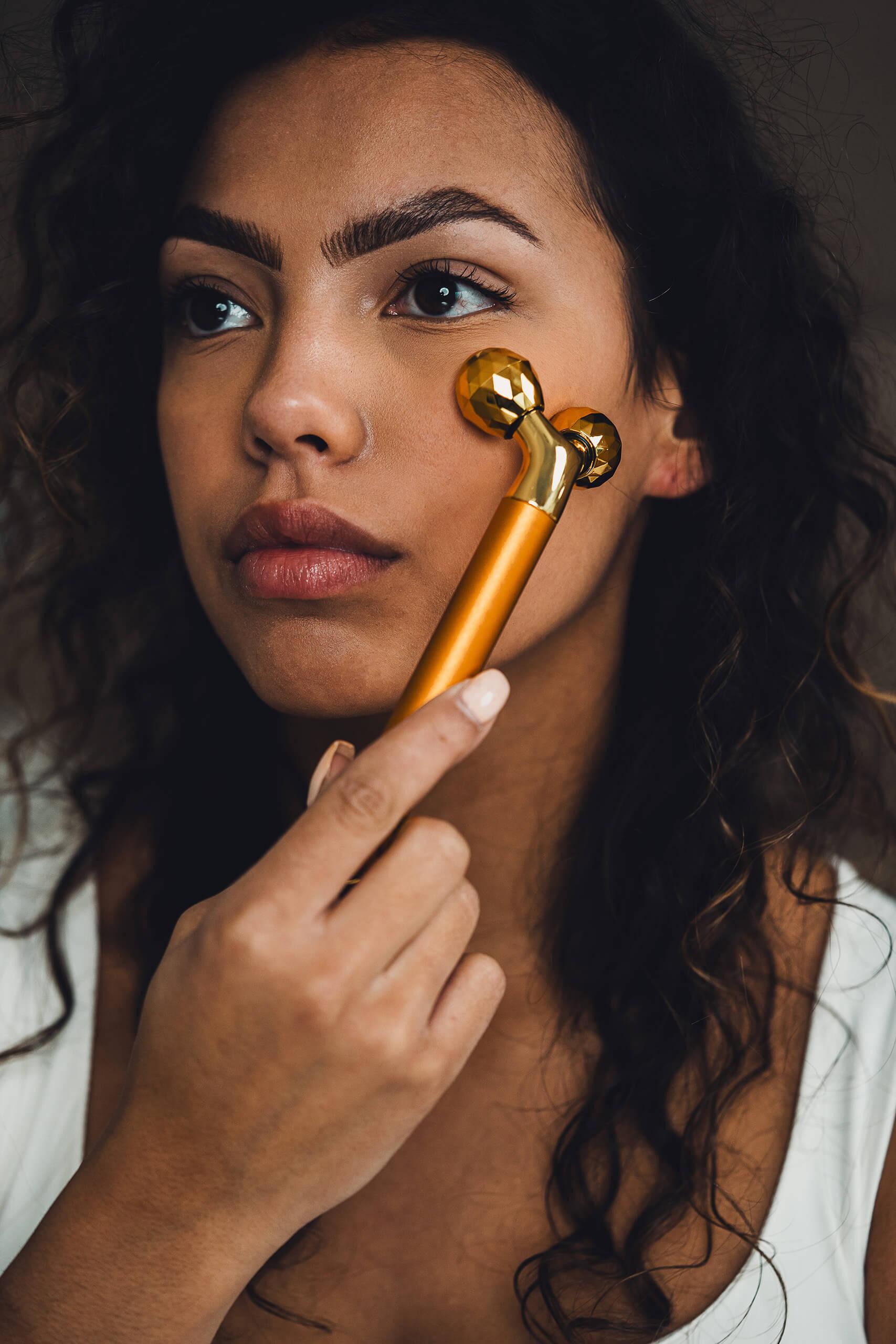 Model met elektrische vibrerende gezichtsroller set goud