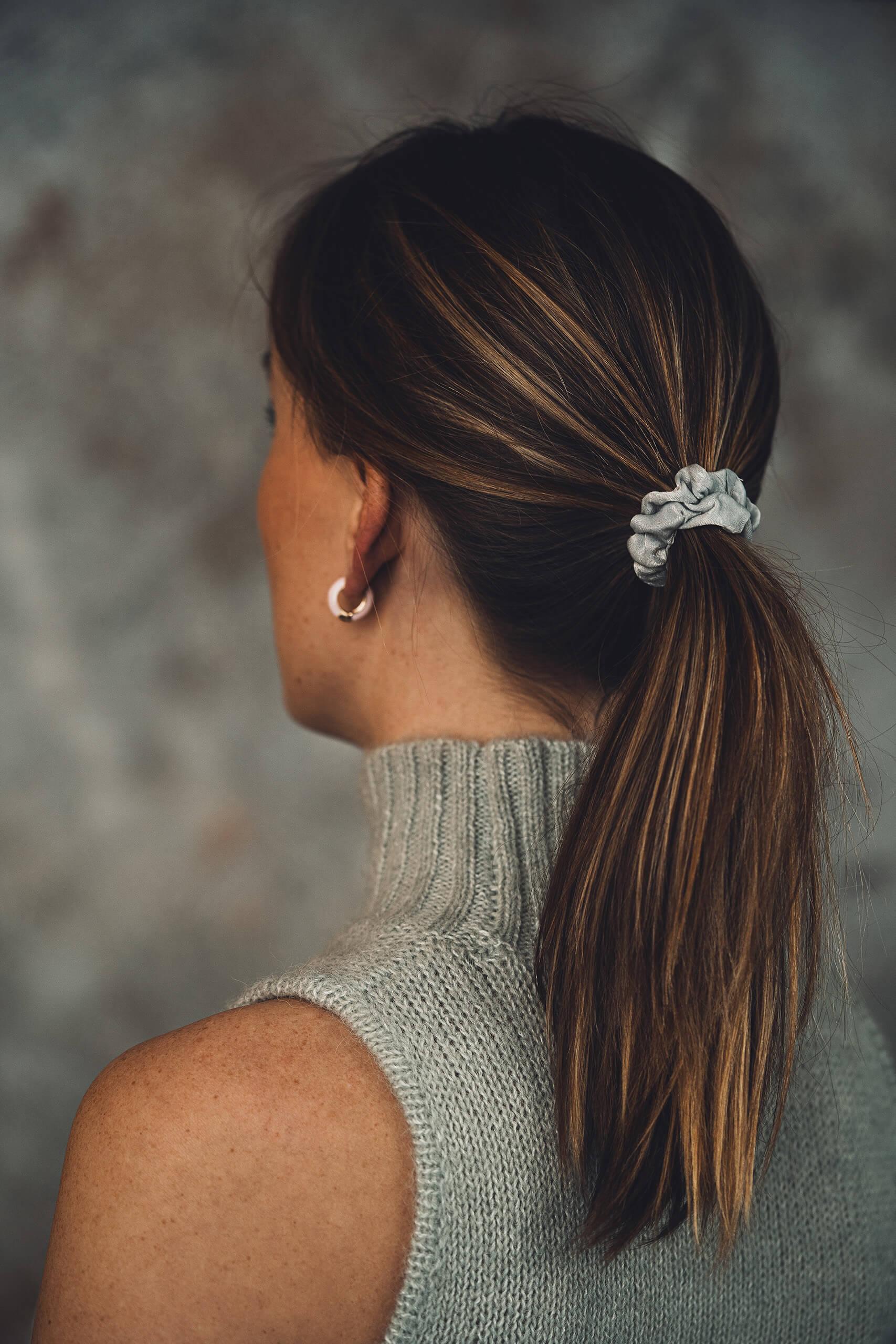 Model met dunne scrunchie lichtgrijs en enamel oorring